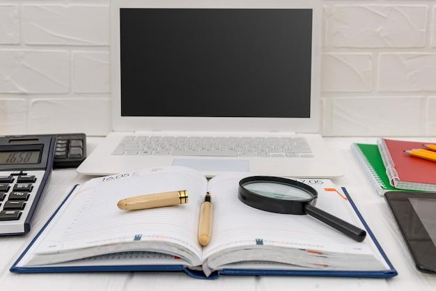 Diário com laptop na mesa, conceito de local de trabalho