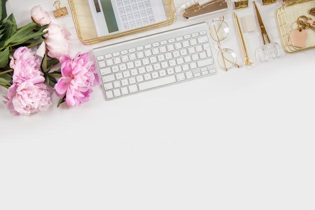 Diário da mulher e artigos de papelaria dourados. buquê de peônias rosa. óculos, teclado branco, caneta, tesoura e café na mesa.