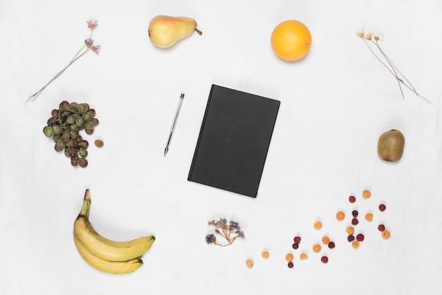 Diário de capa preta fechada e caneta com muitas frutas em pano de fundo branco