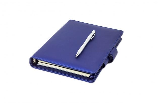 Diário de colarinho azul e caneta colocada na capa e branco