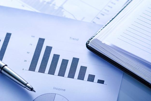 Diário de escritório aberto em um gráfico de barras com caneta