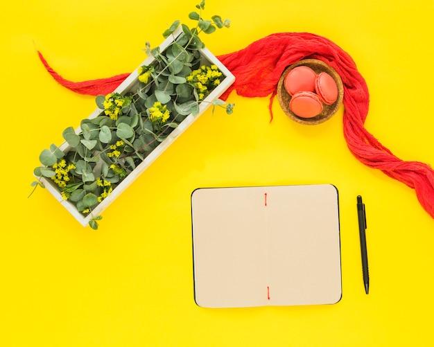 Diário em branco; caneta; têxtil; macaroons e folhas na caixa de madeira contra o pano de fundo amarelo