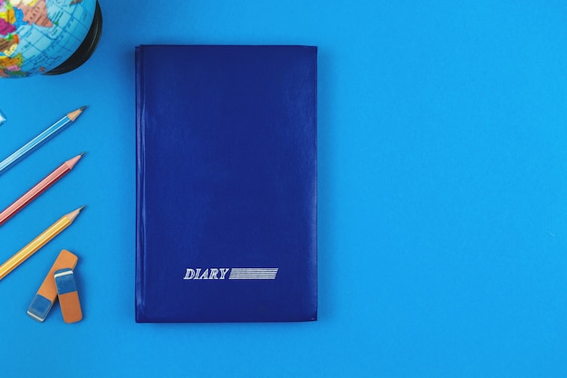 Diário escolar na mesa azul, papelaria escolar volta às aulas, composição plana leiga e foto de fundo com espaço de cópia