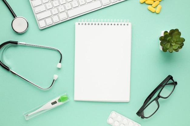 Diário espiral vazio com equipamento médico na mesa do médico