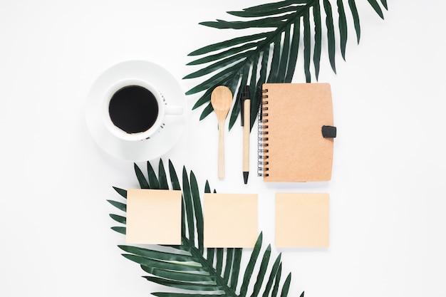 Diário fechado; xícara de café; nota adesiva; colher e caneta com xícara de café em pano de fundo branco