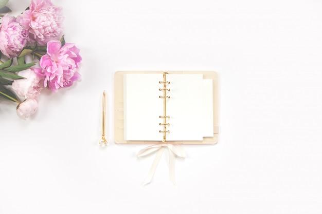 Diário feminino, caneta dourada e peônias rosa sobre fundo branco. copie o espaço.