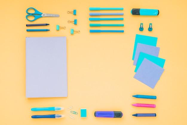 Diário; giz de cera; tesoura com artigos de papelaria do escritório dispostos em pano de fundo laranja