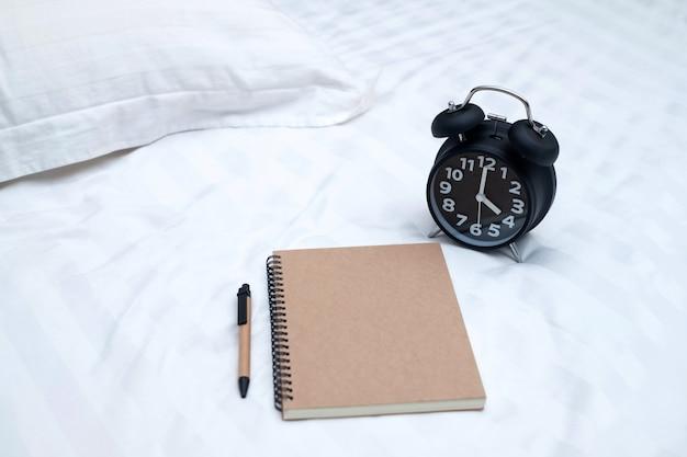 Diário ou notebook e despertador vintage na cama