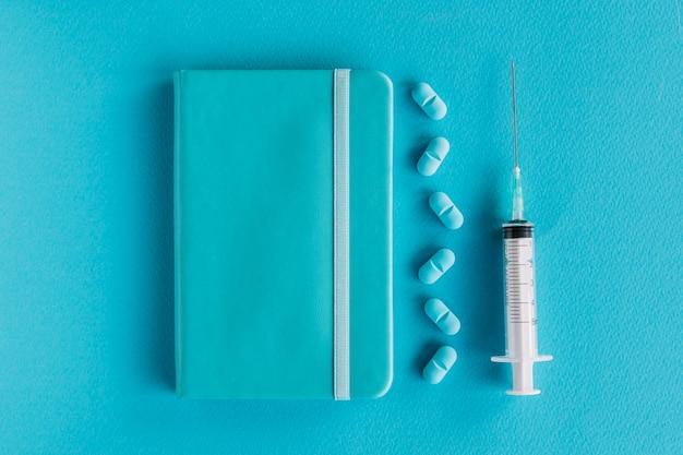 Diário; pílulas e seringa na superfície azul