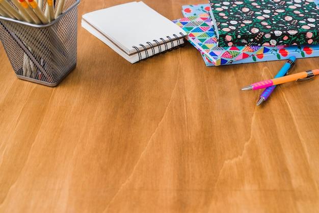 Diários e caderno com canetas e lápis