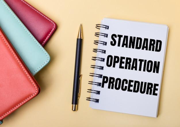 Diários multicoloridos ficam em uma parede bege ao lado de uma caneta e um caderno com as palavras procedimento de operação padrão. postura plana.