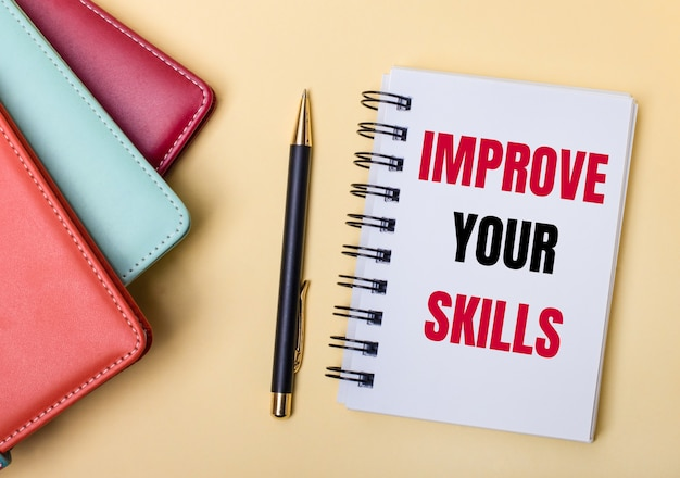 Diários multicoloridos repousam sobre um fundo bege ao lado de uma caneta e um caderno com as palavras melhore suas habilidades