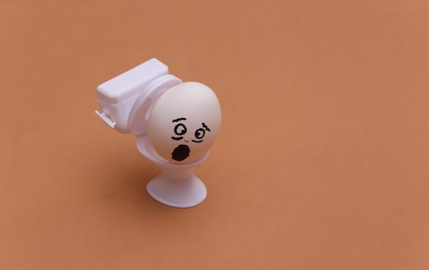 Diarréia ou envenenamento. cara de ovo e mini banheiro em fundo marrom