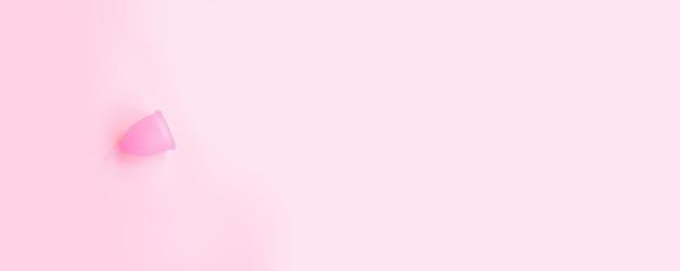 Dias críticos, menstruação. copo menstrual de bio silicone em um fundo rosa.