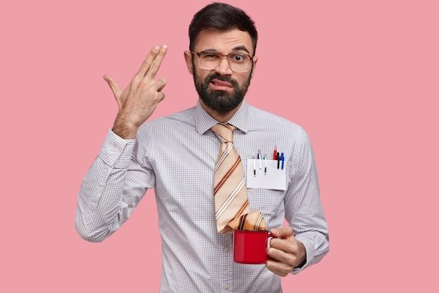 Diasappointed próspero especialista em marketing com barba por fazer dá um tiro na cabeça, sente-se frustrado, tem muito trabalho, usa camisa elegante, canetas no bolso