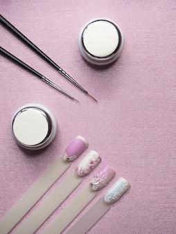 Dicas e tintas para desenhar nas unhas em uma mesa rosa. conceito criativo de manicure.