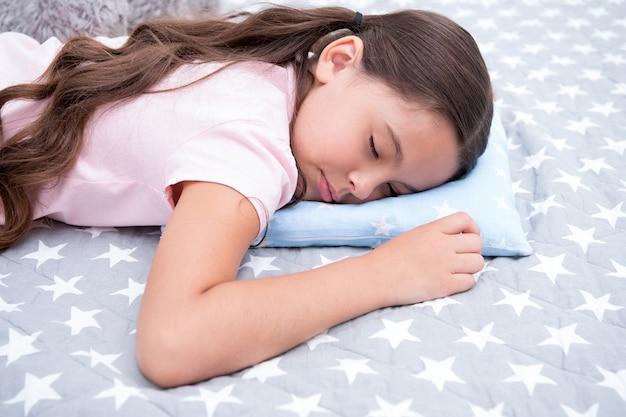 Dicas para um sono saudável. menina dorme no pequeno fundo de roupa de cama com almofada. cabelo comprido de menina criança adormecer travesseiro close-up. a qualidade do sono depende de muitos fatores. escolha um travesseiro adequado para relaxar bem.