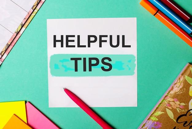 Dicas úteis escritas em uma superfície turquesa perto de adesivos brilhantes, blocos de notas e marcadores