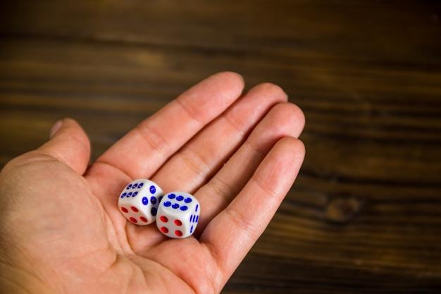 Dices brancos na mão feminina contra closeup de mesa de madeira. conceito de cassino, jogo e fortuna