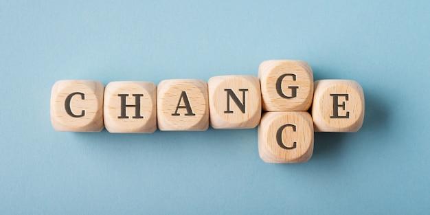 Dices de madeira que soletram palavras mudança e possibilidade