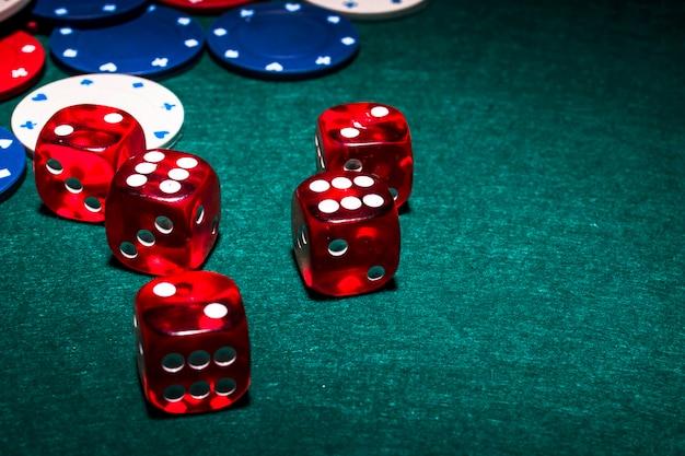 Dices vermelhos brilhantes na mesa de poker verde