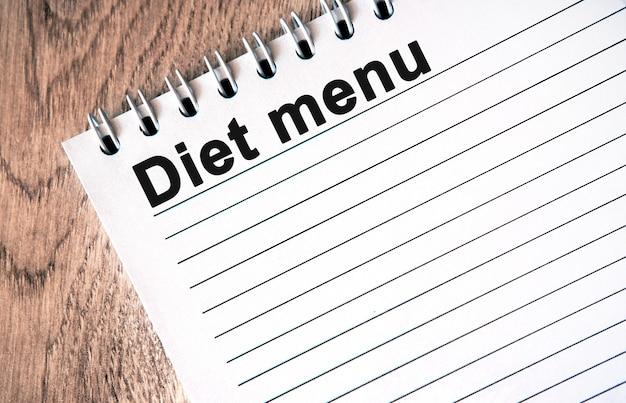 Diet menu - texto preto em um caderno branco com linhas em uma mesa de madeira