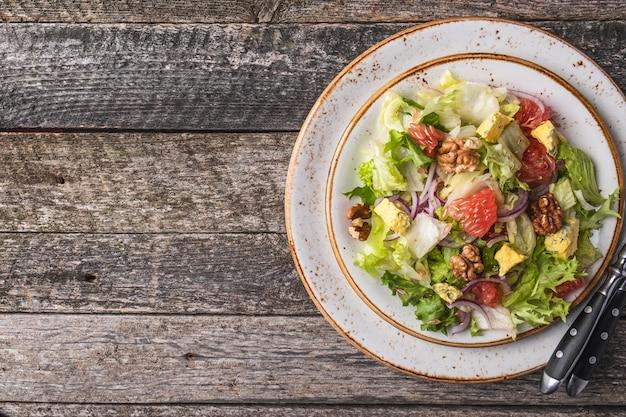 Diet salada garpefruit, queijo, alface e nozes em um prato. dieta e salada saudável. vista do topo