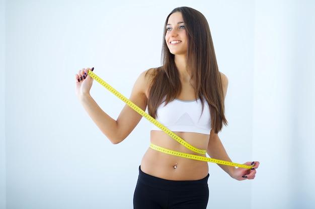 Dieta. a garota tomando medidas de seu corpo
