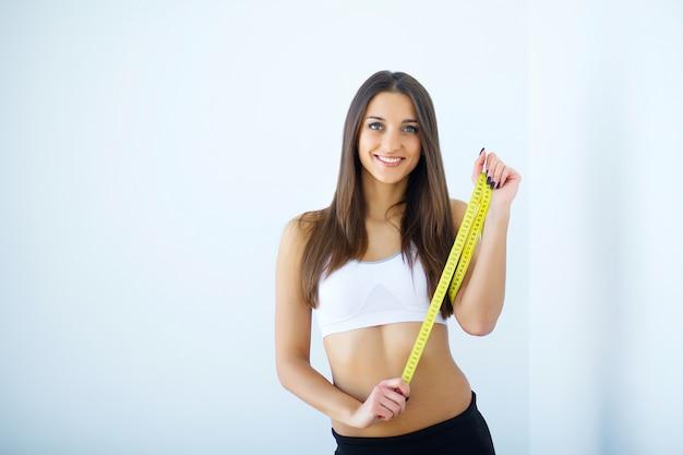 Dieta. a menina que toma medidas de seu corpo, fundo branco.