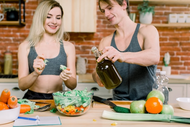 Dieta, alimentação saudável, estilo de vida fitness, nutrição adequada. casal consciente de saúde cozinhar jantar de baixa caloria na cozinha de casa. um homem derrama azeite em uma salada