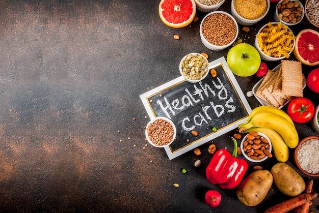 Dieta alimentar conceito de plano de fundo, produtos de carboidratos saudáveis (carboidratos) - frutas, legumes, cereais, nozes, feijão, vista superior do fundo de concreto azul escuro
