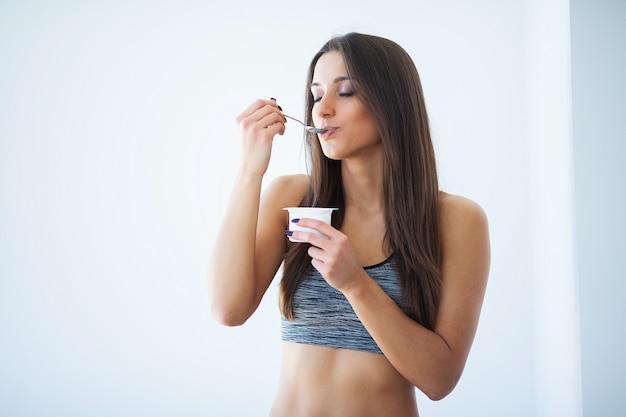 Dieta. bela jovem comer iogurte na cozinha em casa