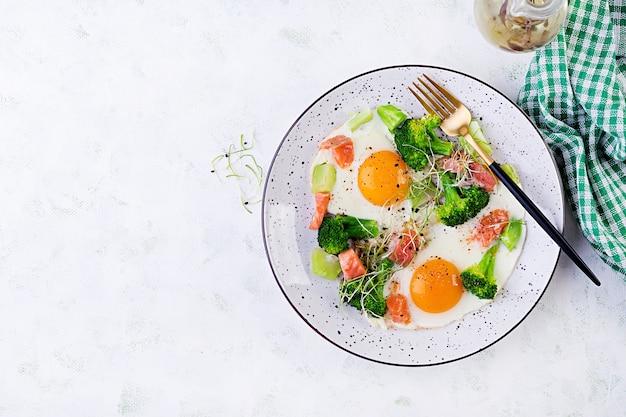 Dieta cetogênica / paleo. ovos fritos, salmão, brócolis e microgreen. café da manhã keto. escovar. vista superior, sobrecarga