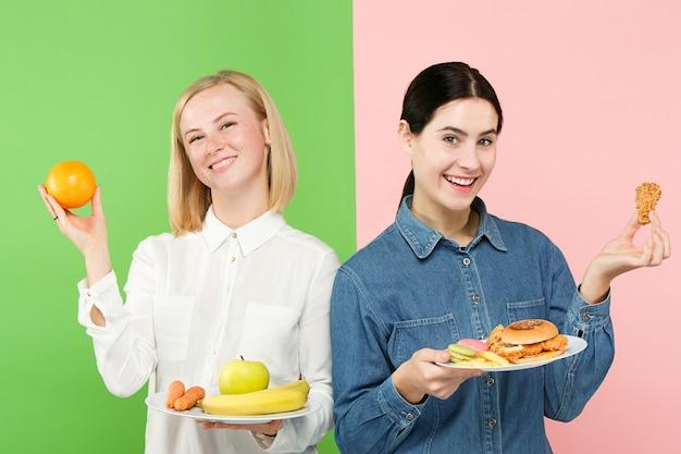 Dieta. conceito de dieta. comida saudável. jovens mulheres bonitas que escolhem entre frutas e fast food deselegante