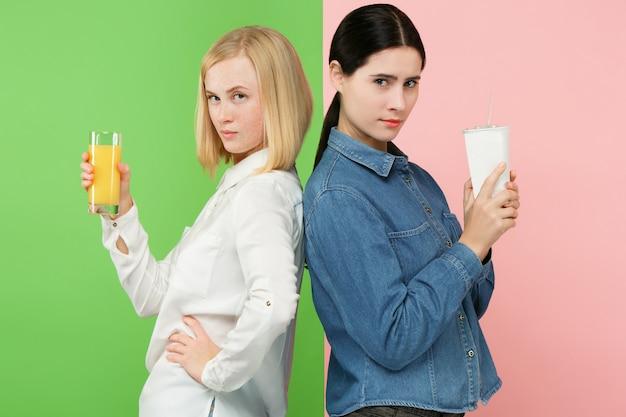 Dieta. conceito de dieta. comida saudável. jovens mulheres bonitas que escolhem entre o suco de laranja e a bebida doce não carbonatada