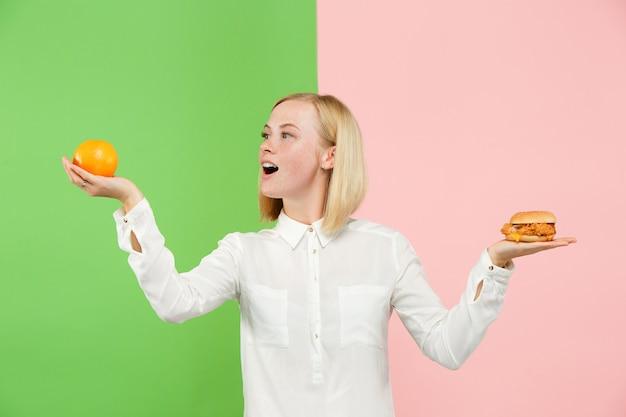 Dieta. conceito de dieta. comida saudável. mulher jovem e bonita escolhendo entre frutas e fast food deselegante