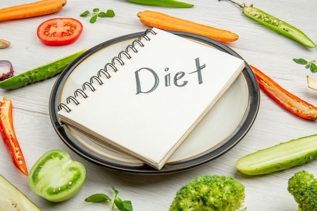 Dieta da vista inferior escrita no bloco de notas no prato, corte de vegetais na mesa cinza