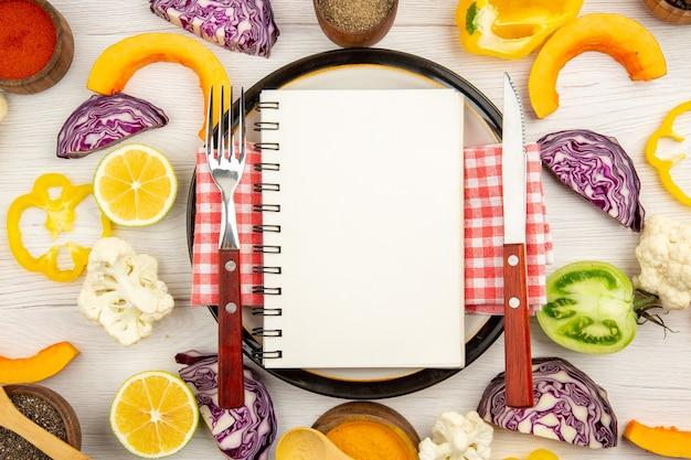 Dieta da vista superior escrita no bloco de notas, garfo e faca no prato redondo, corte de vegetais diferentes especiarias em tigelas na mesa de madeira branca
