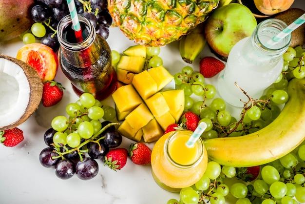 Dieta de vitaminas de verão diferentes sucos de frutas conceito de dieta com frutas tropicais e frutas sobre um fundo claro