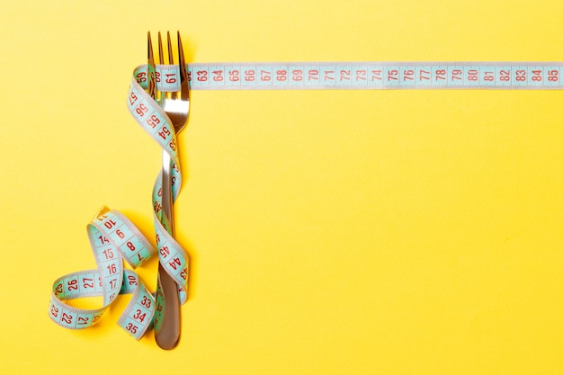 Dieta e alimentação saudável. garfo e fita métrica em fundo amarelo.