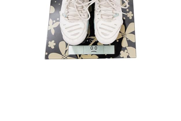 Dieta e peso, close-up de pernas femininas de tênis em pé na balança. fundo branco.