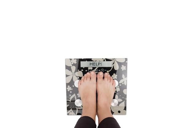 Dieta e peso, uma jovem de pé em uma balança, apenas as pernas são visíveis. fundo branco. copie o espaço.
