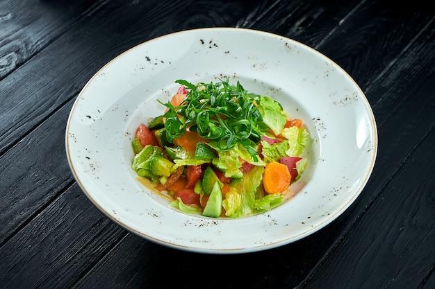 Dieta e salada vegetariana de vegetais mistos e alface com molho de amendoim, servida em um prato branco sobre fundo preto de madeira