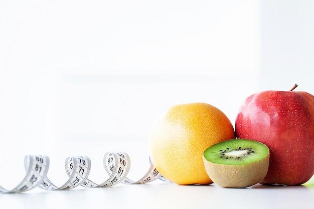 Dieta. fitness e conceito de dieta alimentar saudável. dieta balanceada com legumes. vegetais verdes frescos, fita métrica. fechar-se