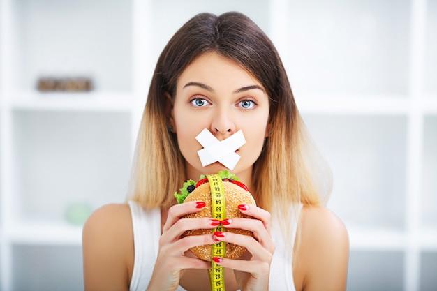 Dieta. jovem mulher bonita comendo hambúrguer