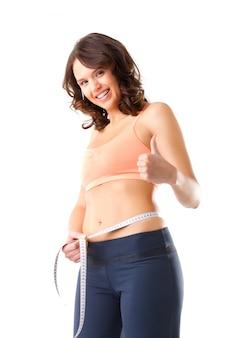 Dieta - jovem mulher está medindo a cintura dela