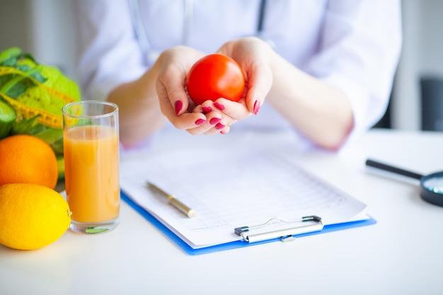 Dieta. médico nutricionista segurar tomate. conceito de comida natural e estilo de vida saudável. fitness e conceito de dieta alimentar saudável. dieta equilibrada com legumes.