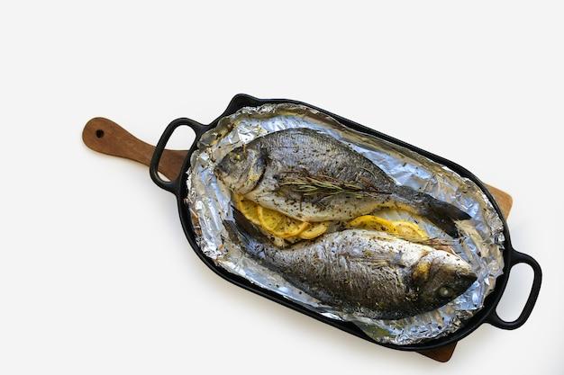 Dieta mediterrânea dourada assada com limão e ervas assada dorada em uma assadeira dorada nutrição adequada peixe cozido em um prato branco com espaço de redação dorada cozida no forno peixe assado