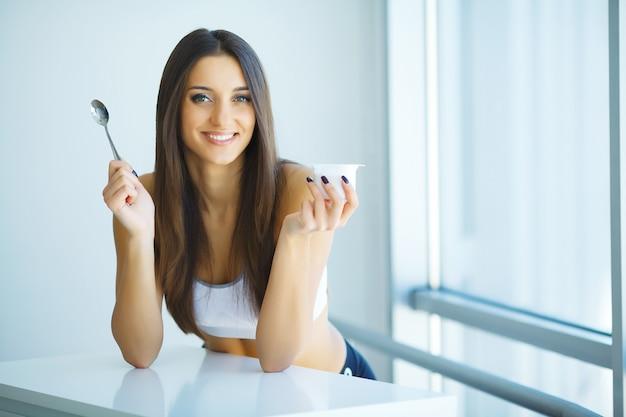 Dieta. mulher jovem feliz comendo iogurte na cozinha