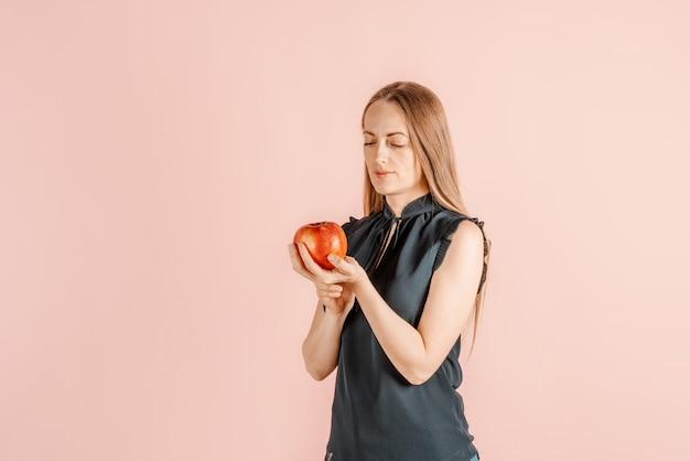 Dieta, nutrição mais saudável. menina bonita, segurando uma maçã nas mãos, parede rosa. a alegria de um estilo de vida saudável. fruta.